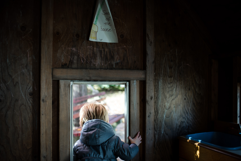 Little boy walking through doorway of playhouse.
