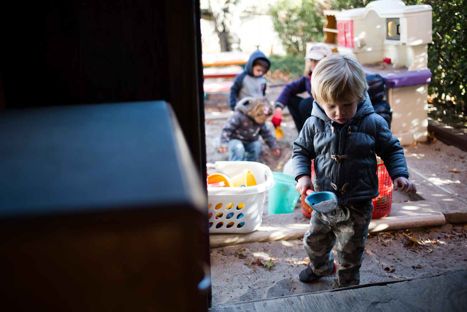 Kids playing in sand box at nursery school.