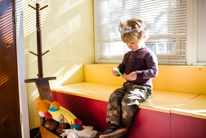 Little boy dressed in a princess crown.
