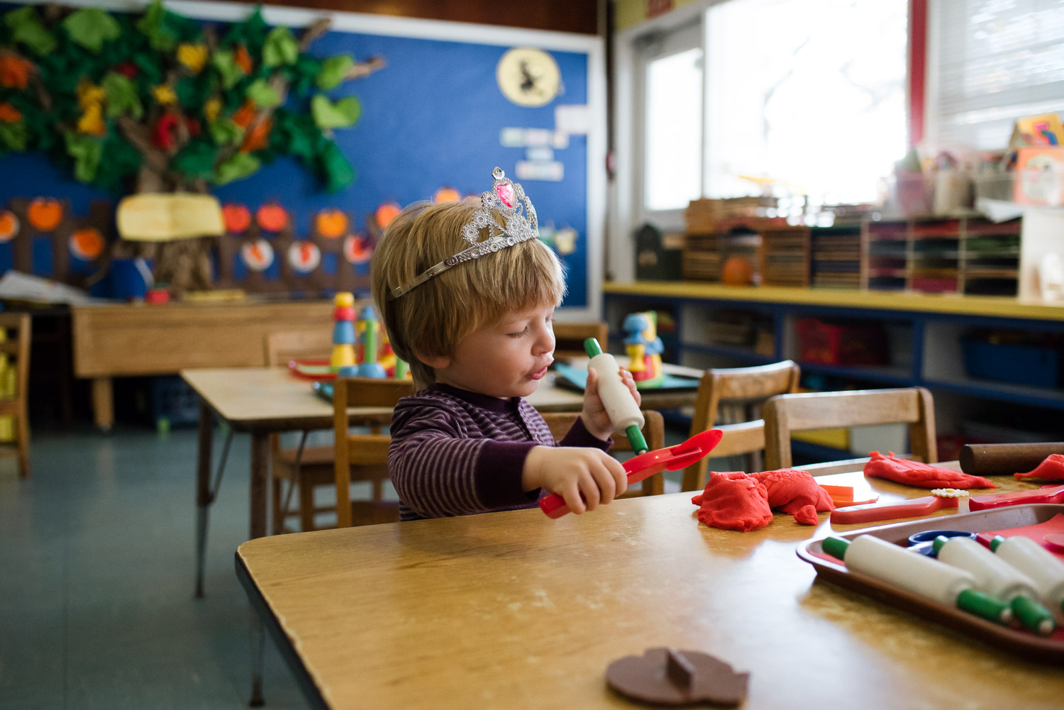 Little boy playing with play doh at nursery school.