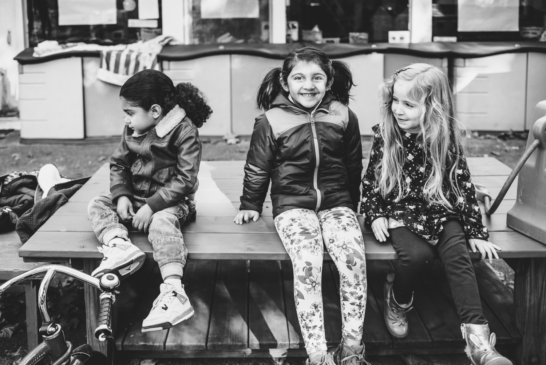 Kids sitting on a bench at nursery school.