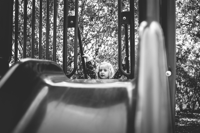 A little girl climbing the slide.
