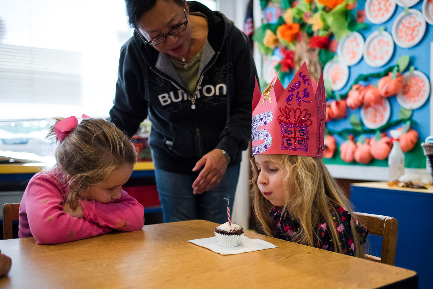 A little girl blowing out the candle on her birthday cupcake.