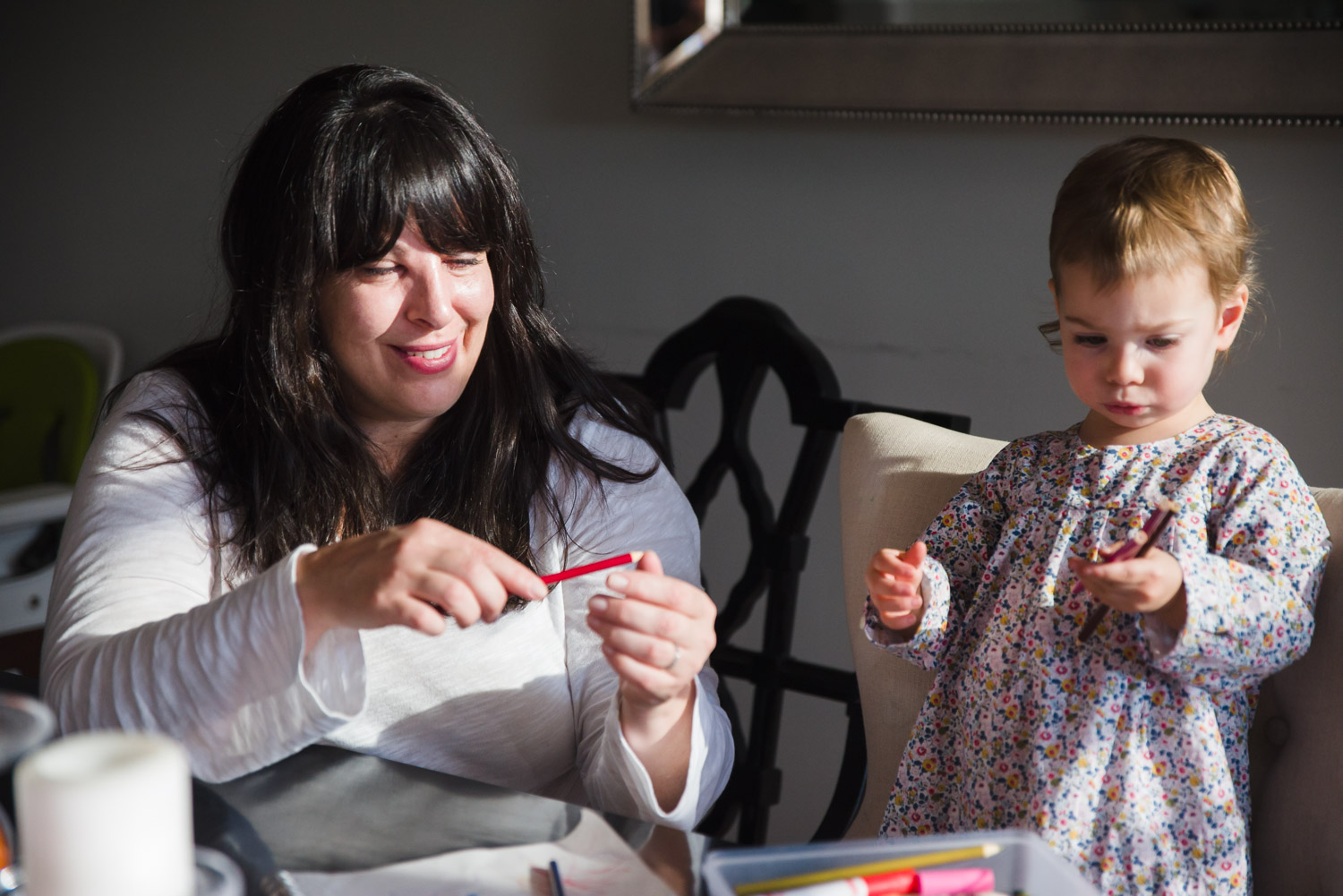 Mother and daughter coloring at the kitchen table.