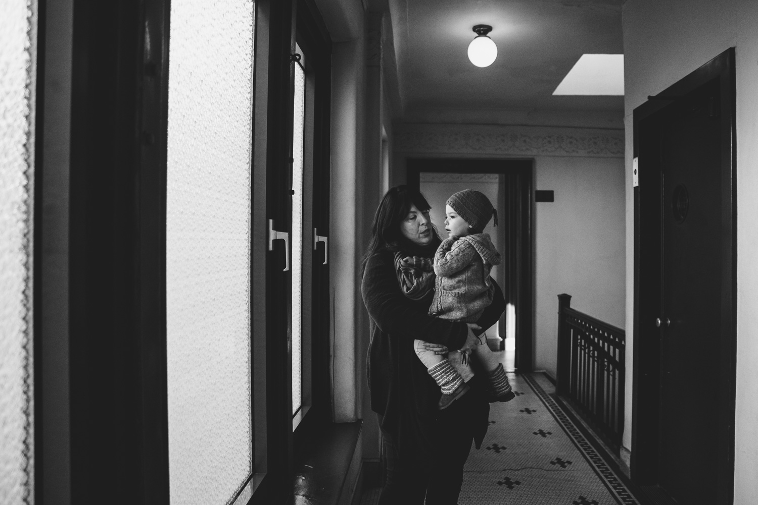 Mother holding toddler while waiting for the elevator.