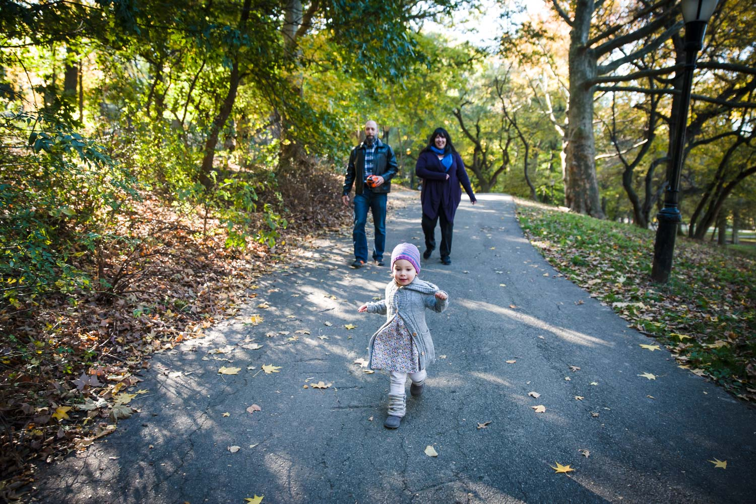 Toddler girl running down a hill with parents following.
