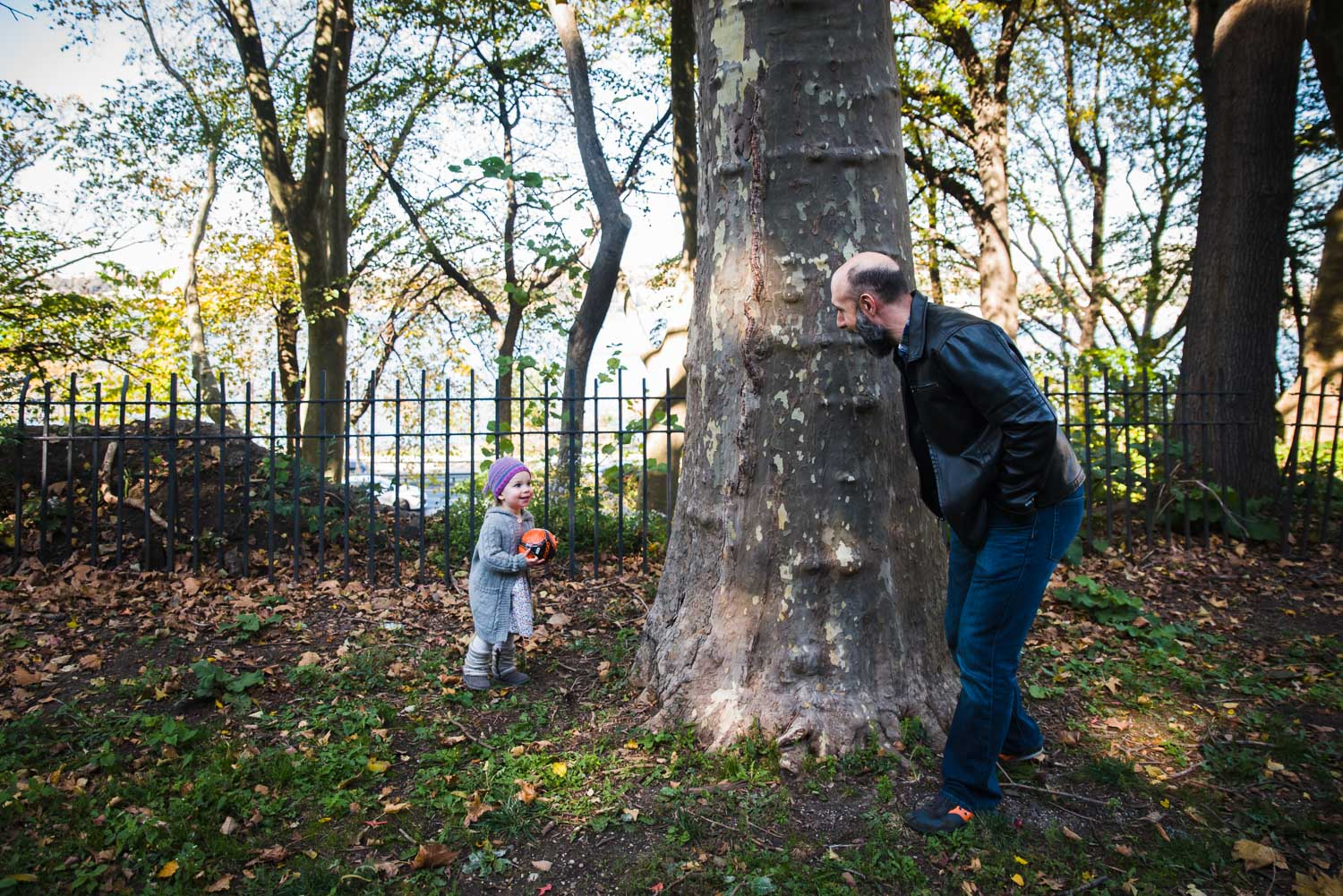 Dad playing hide and go seek with daughter in Riverside Park.