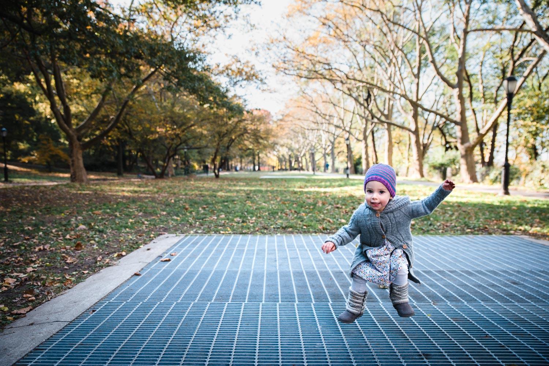 Little girl jumping on grate at Riverside Park.