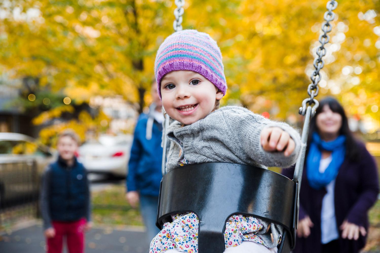 Toddler girl smiling as she swings on a swing.