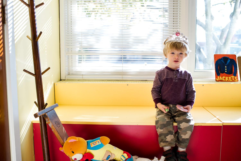 Little boy in a princess crown at nursery school.