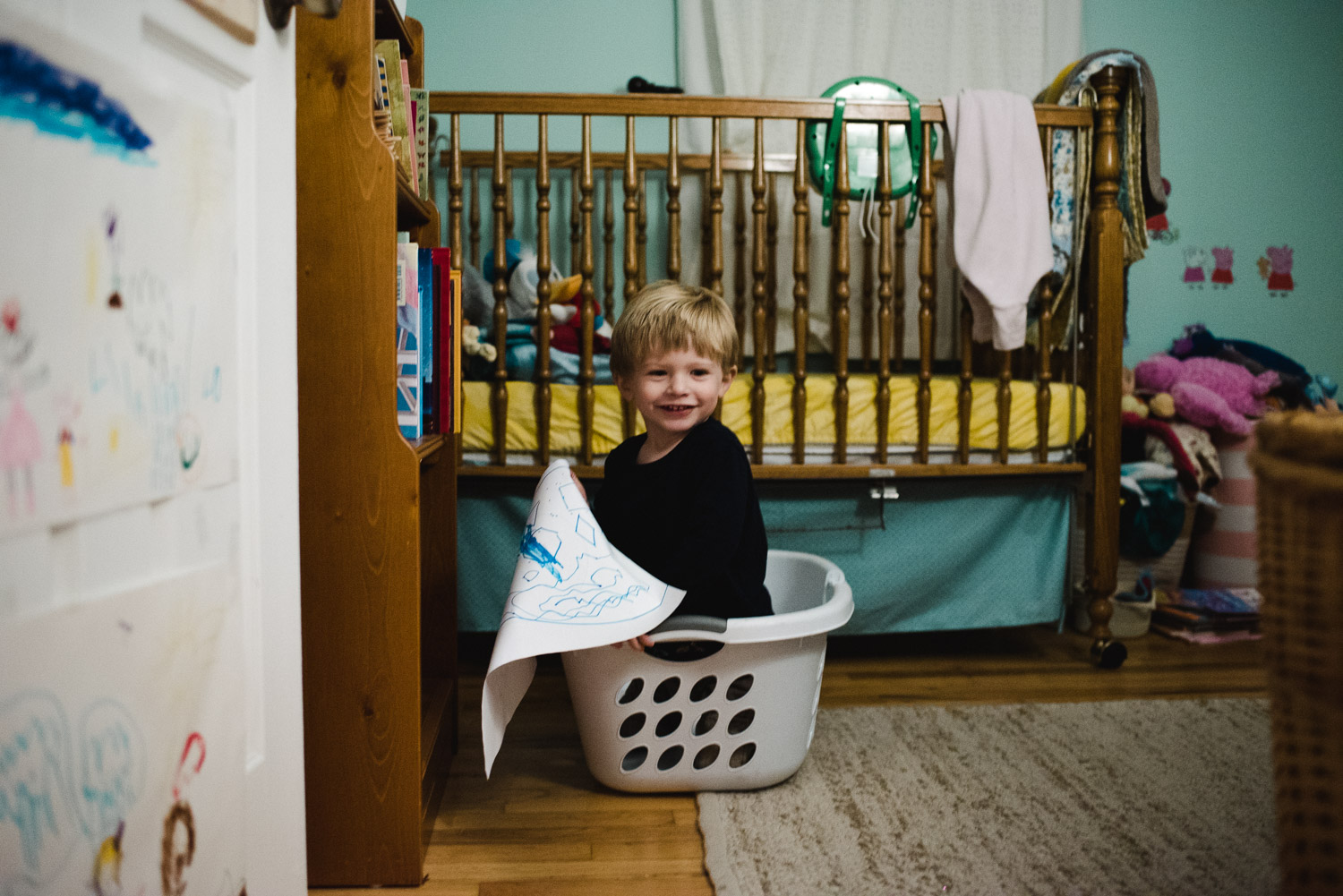 Toddler boy playing in a laundry basket.