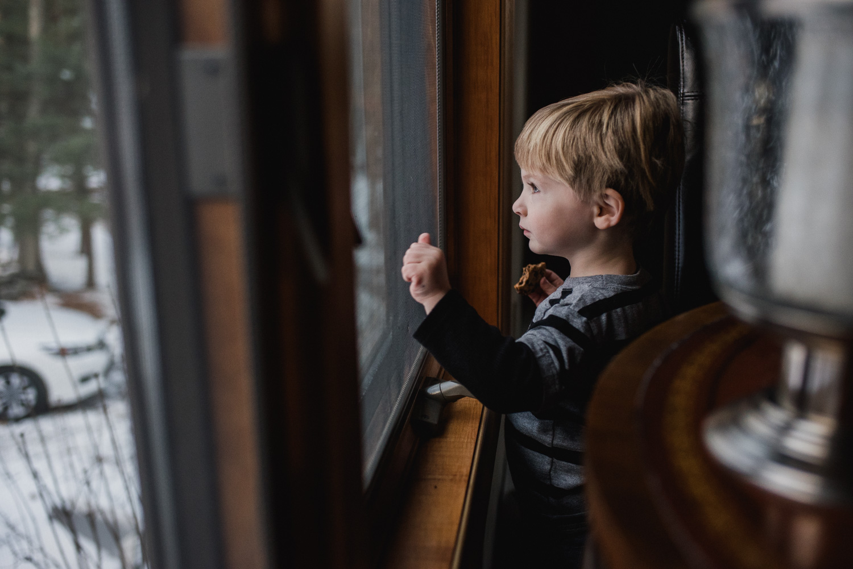 Little boy knocking on a window.