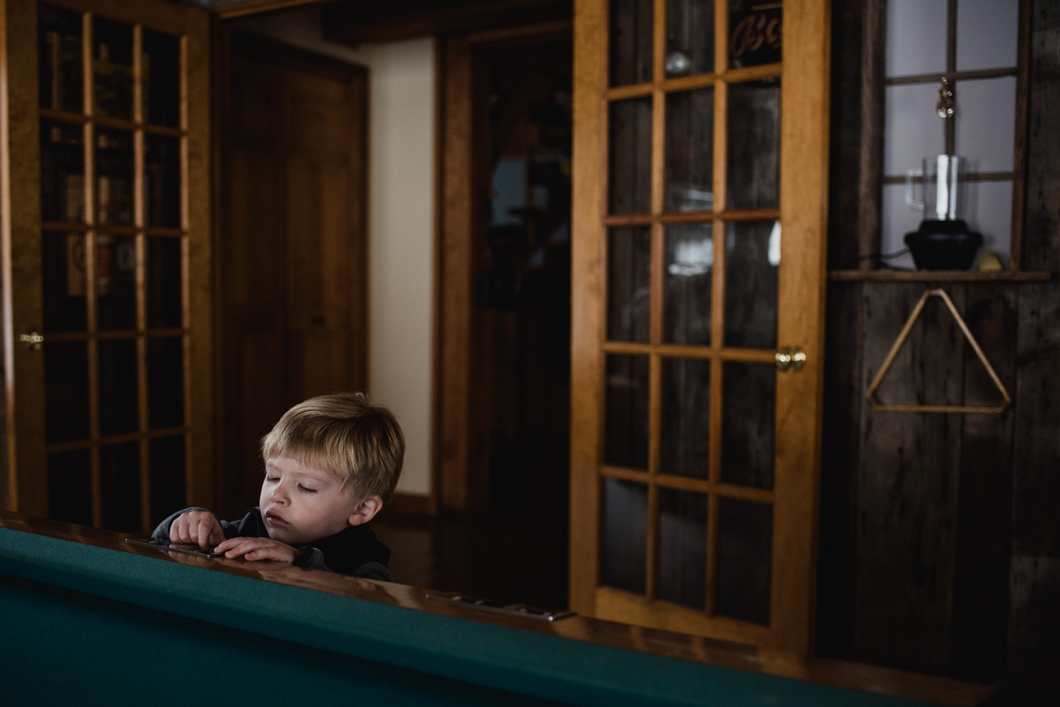 Little boy reaching up to pool table.