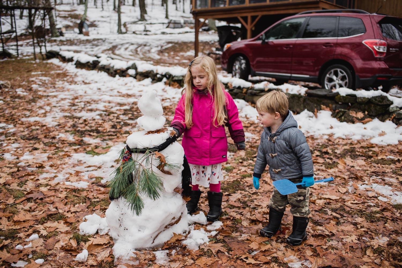 Kids visiting a melting snowman.