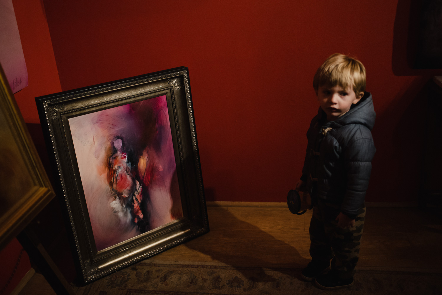 Little boy looking at a painting in an art gallery.