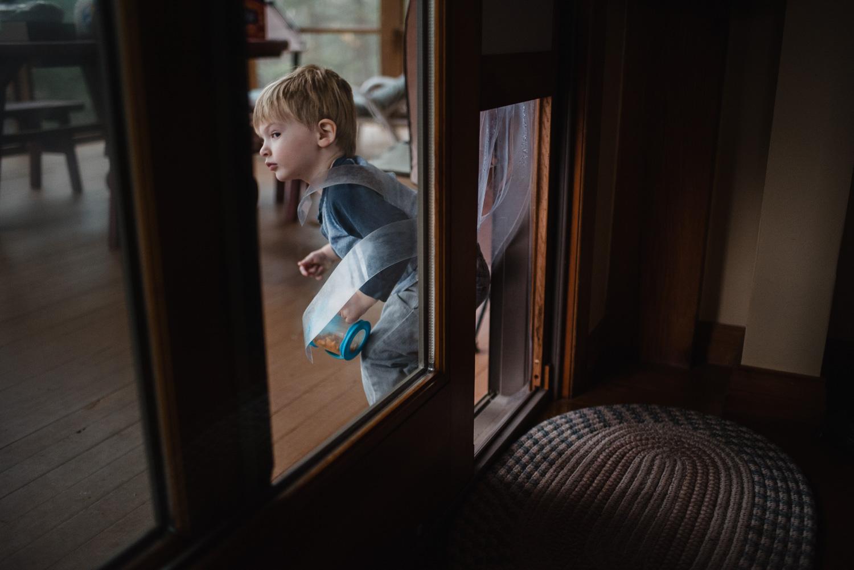 Little boy sneaking through doggie door.