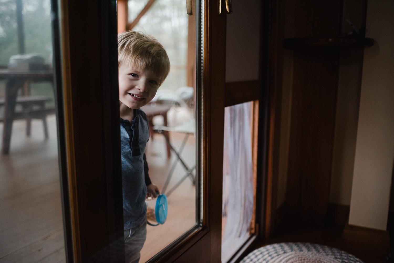Little boy smiling through sliding glass door.