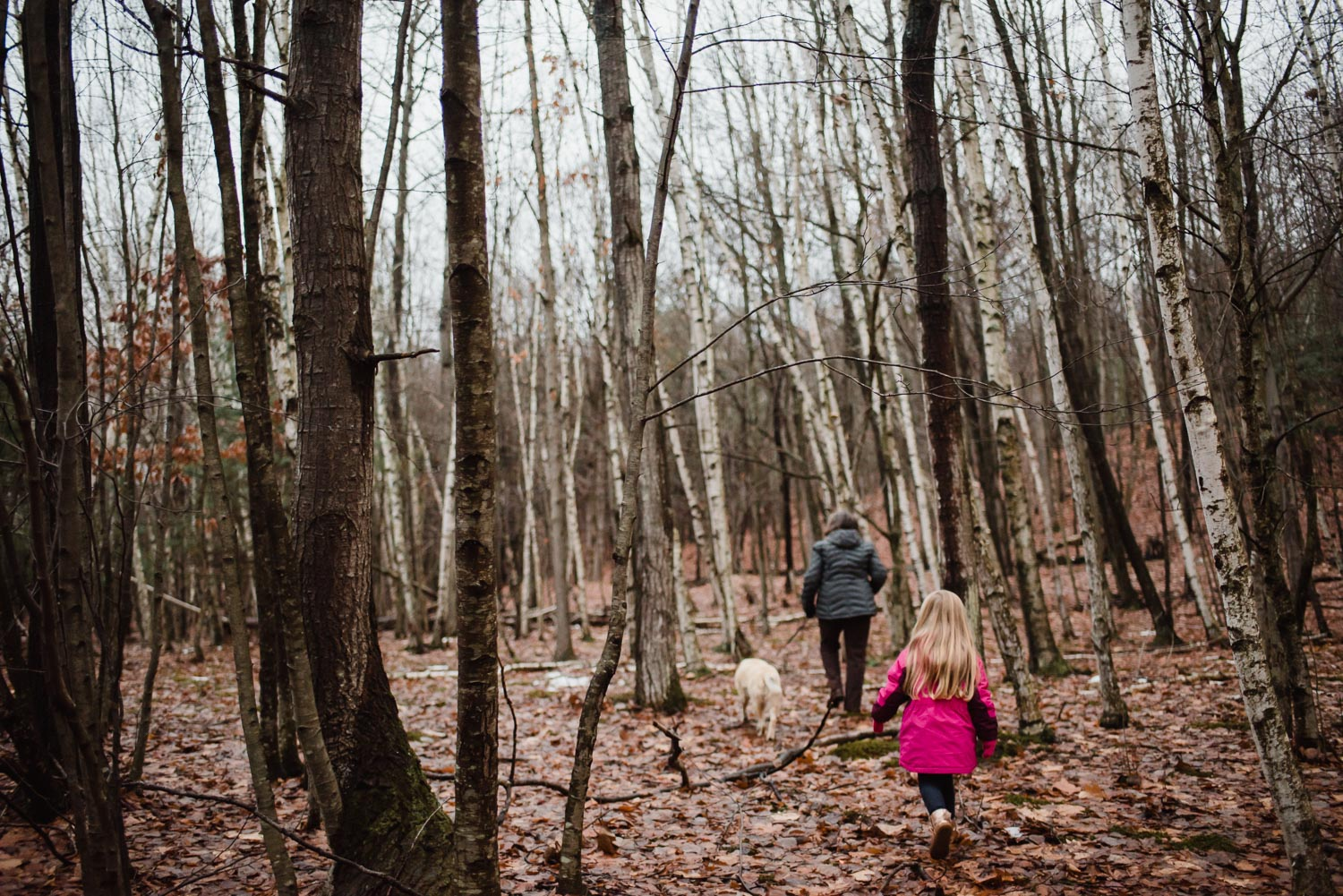 Grandmother and granddaughter walk through the woods.