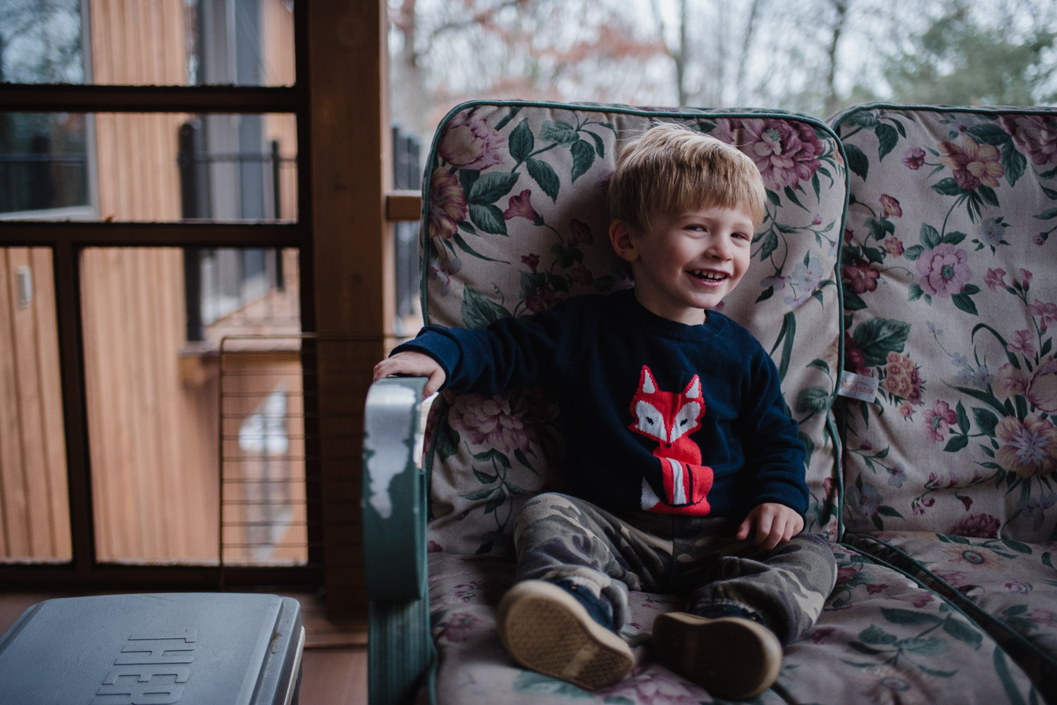 Little boy sitting on rocking chair on porch in Copake, NY.