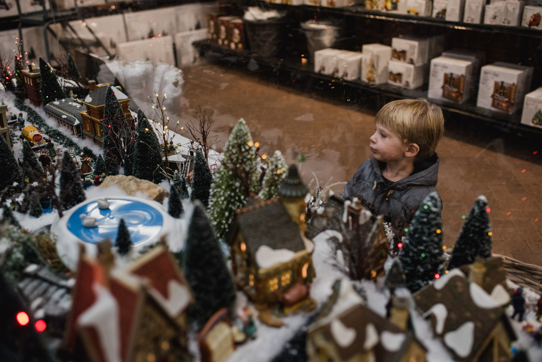 Little boy looking at a miniature train set.