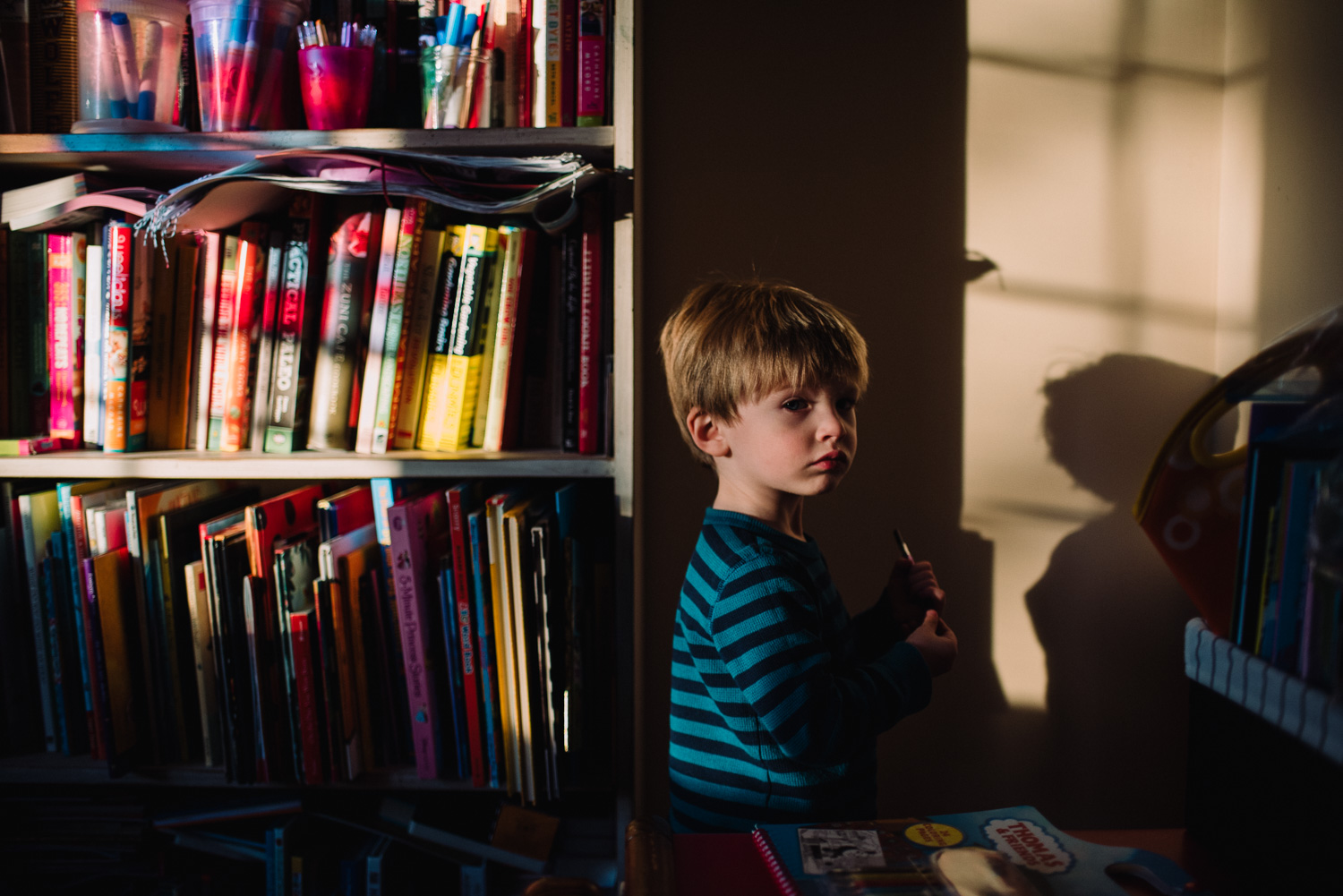 Little boy standing in the light and shadow of afternoon light.