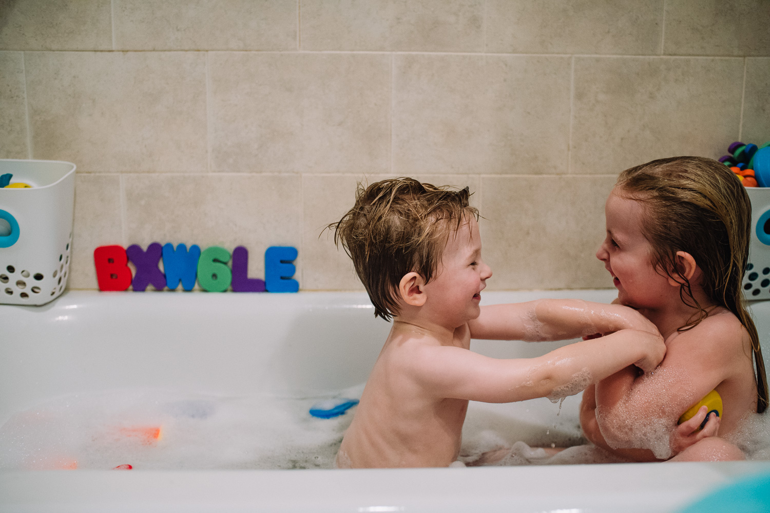 A brother and sister playing around in the bath.