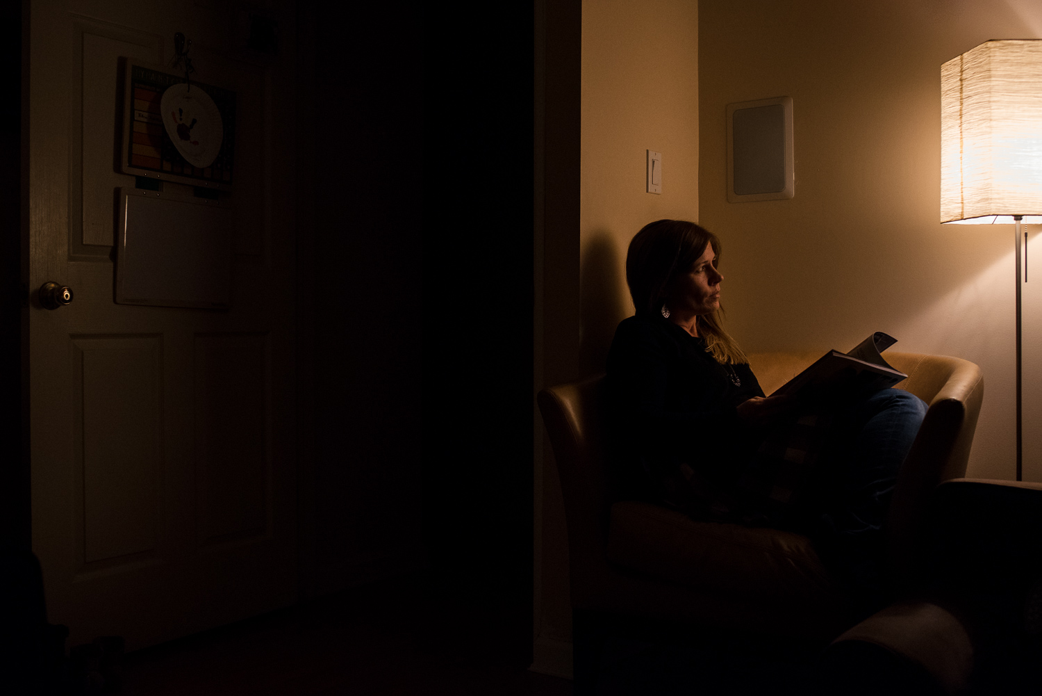 A woman looking at a magazine in low light.