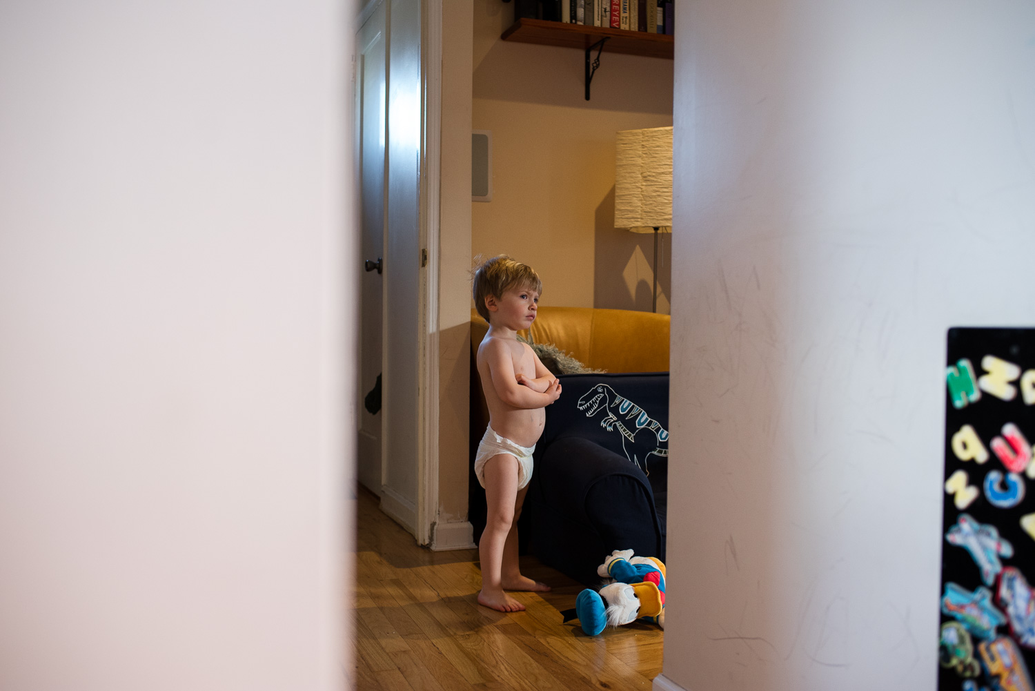 A toddler boy in only a diaper stands and watches TV.