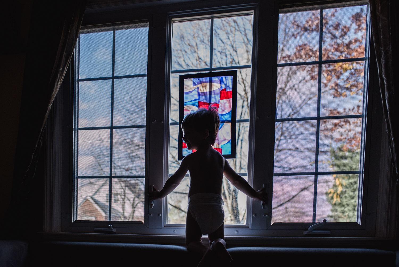 A little boy perches on a window sill.