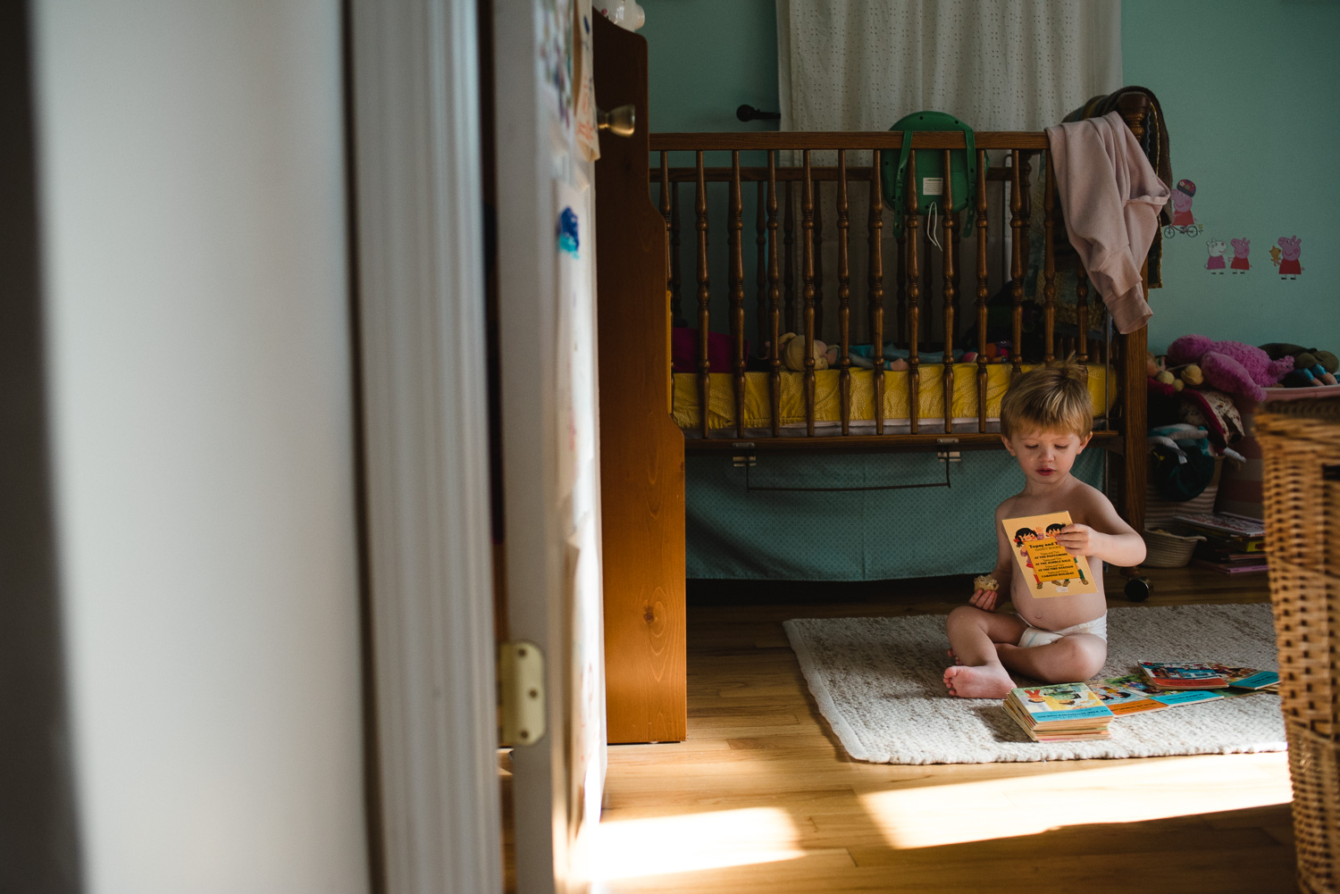 Toddler boy reading a book in his room.