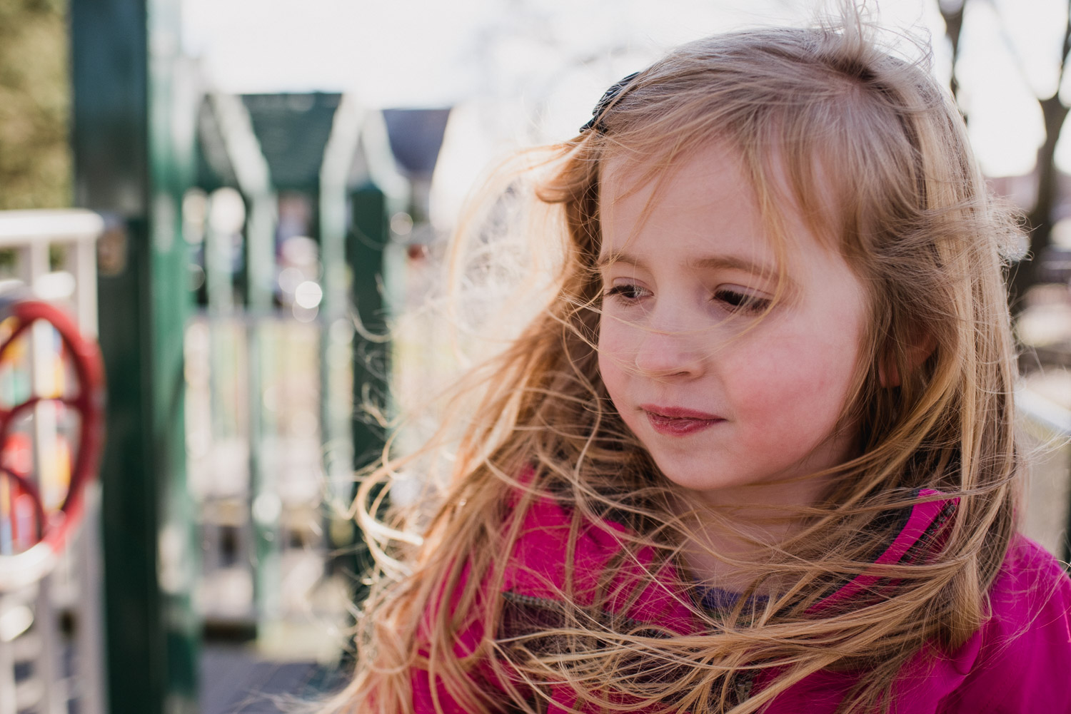 A little girl at the park on a windy day.