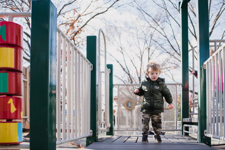 Little boy jumping on playground equipment.