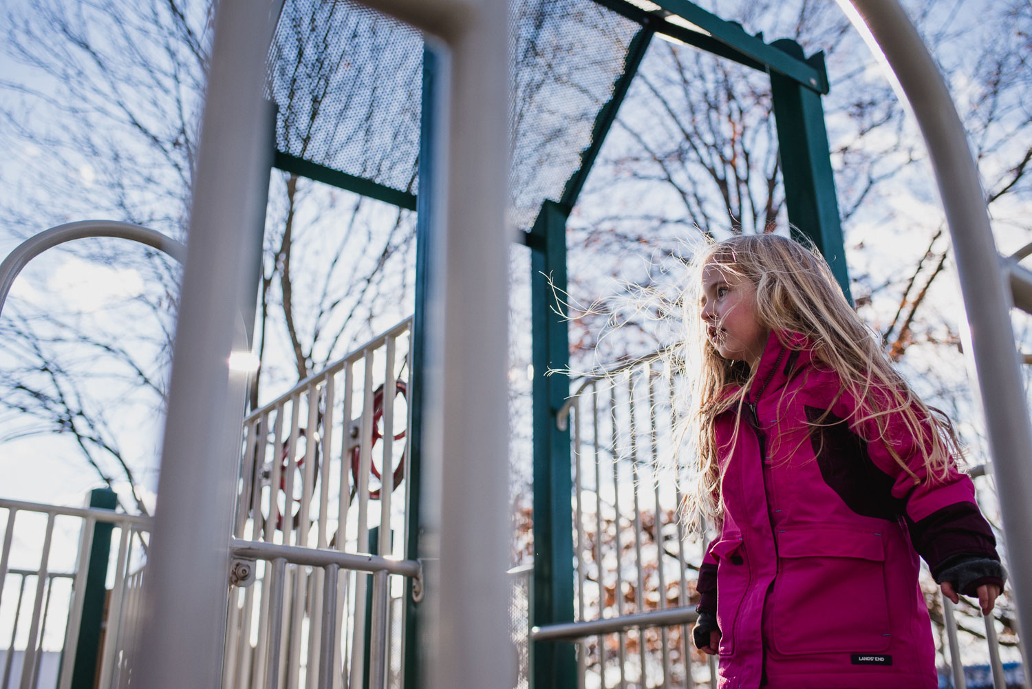 A little girl walking on playground equipment on a cold day.