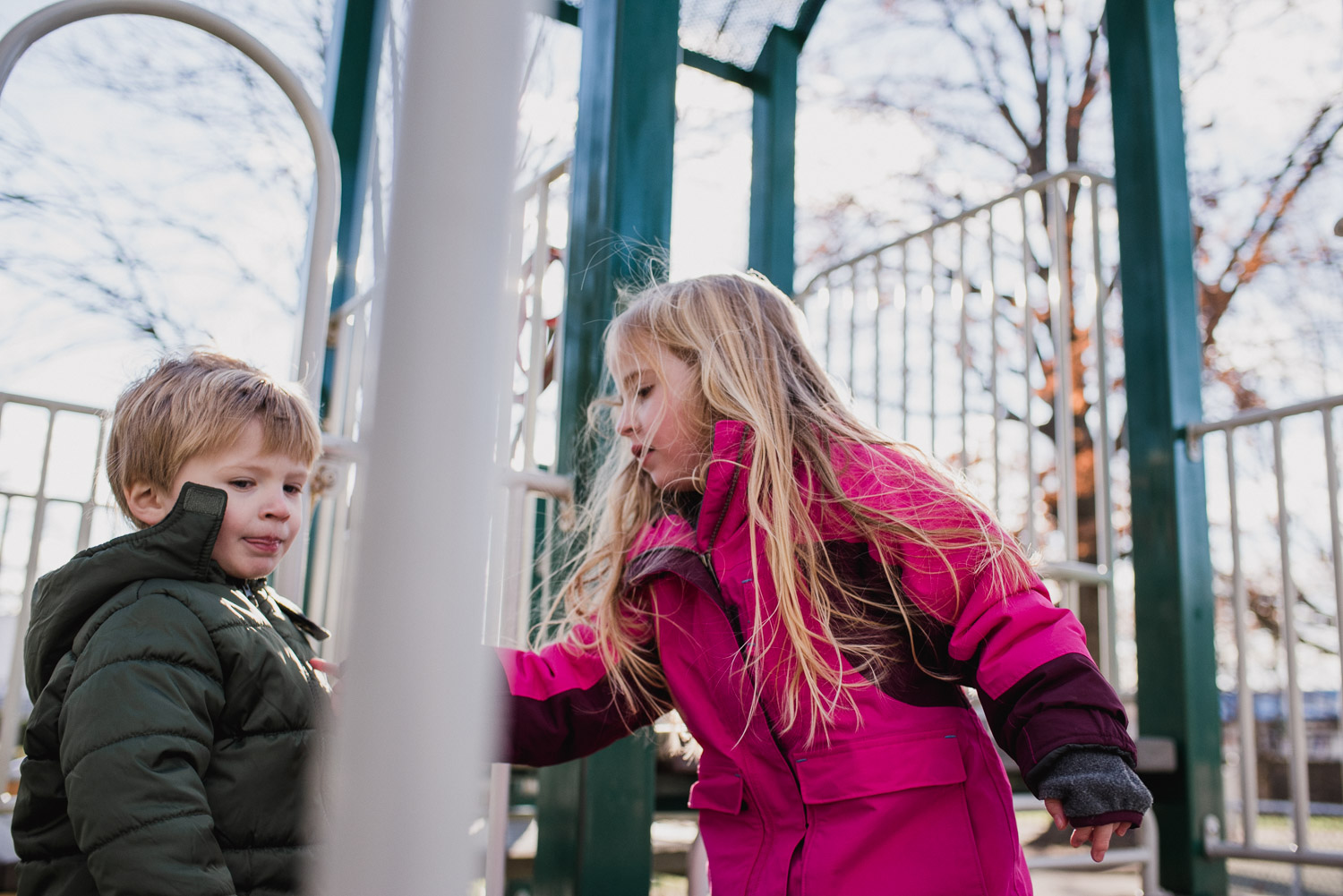 A boy and girl playing on playground equipment on a cold day.