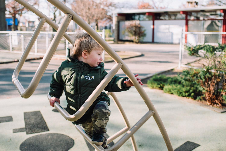 Little boy climbing a ladder on the playground.