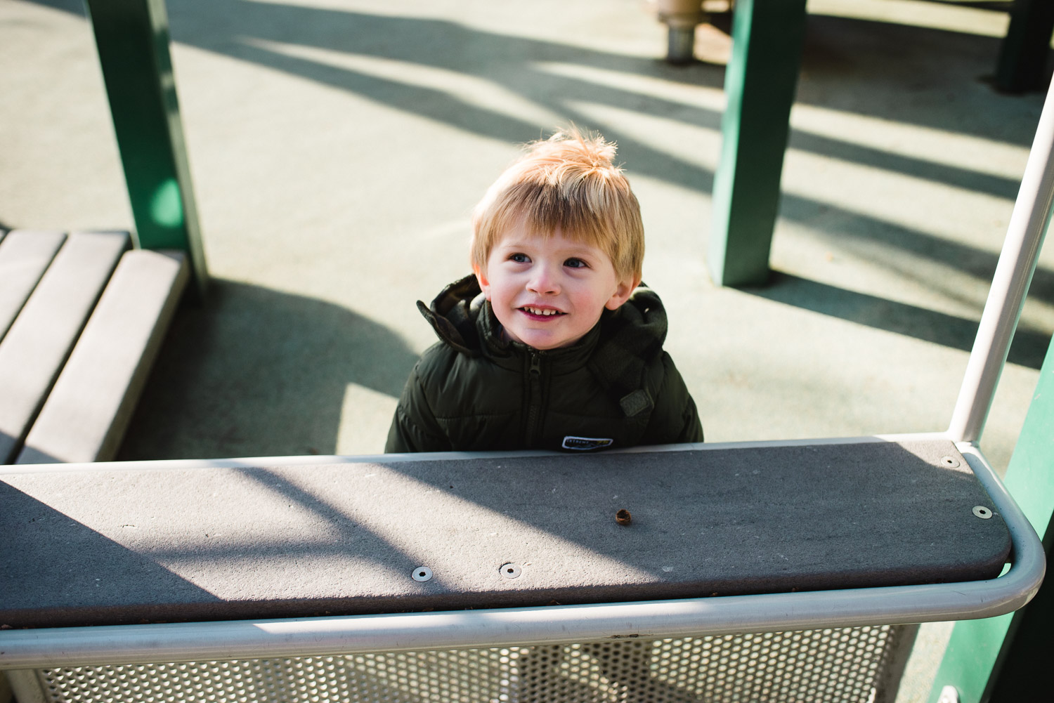 A little boy smiling on the playground.