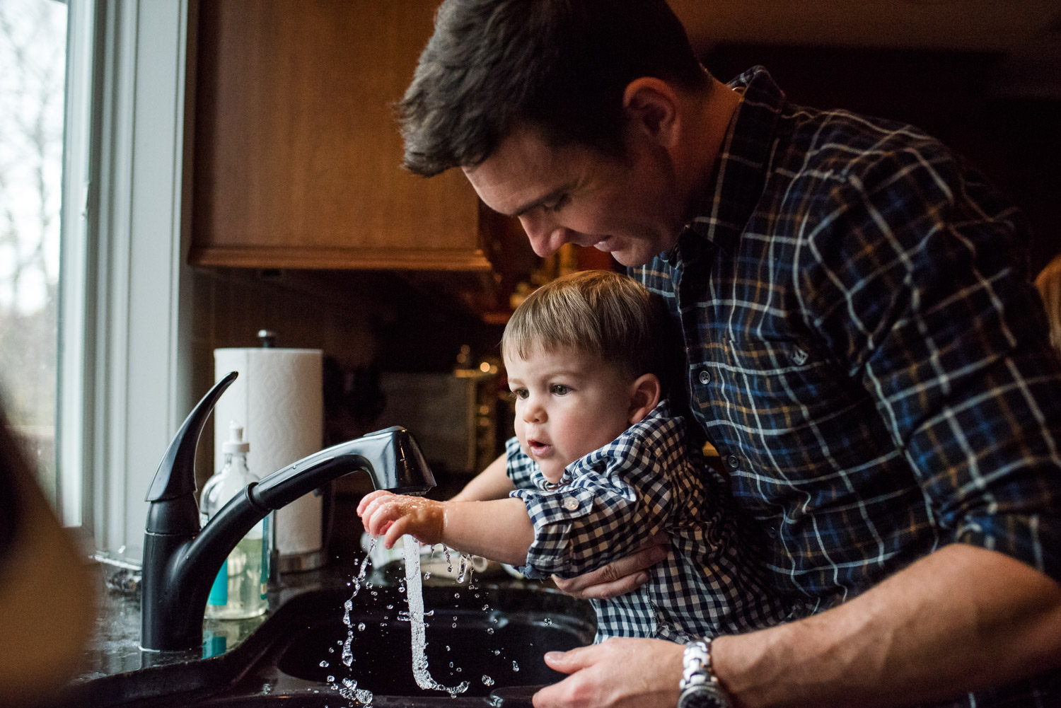 A father helps his baby son wash his hands in the kitchen sink.
