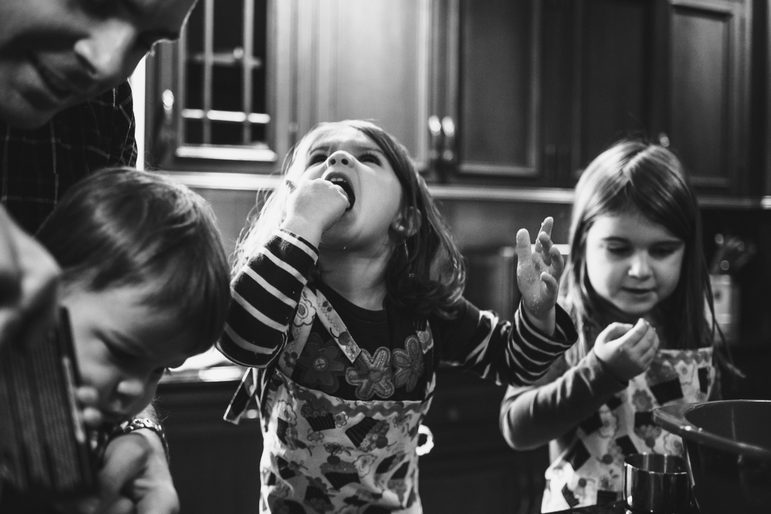 A little girl shoves a handful of cookie dough in her mouth while baking.