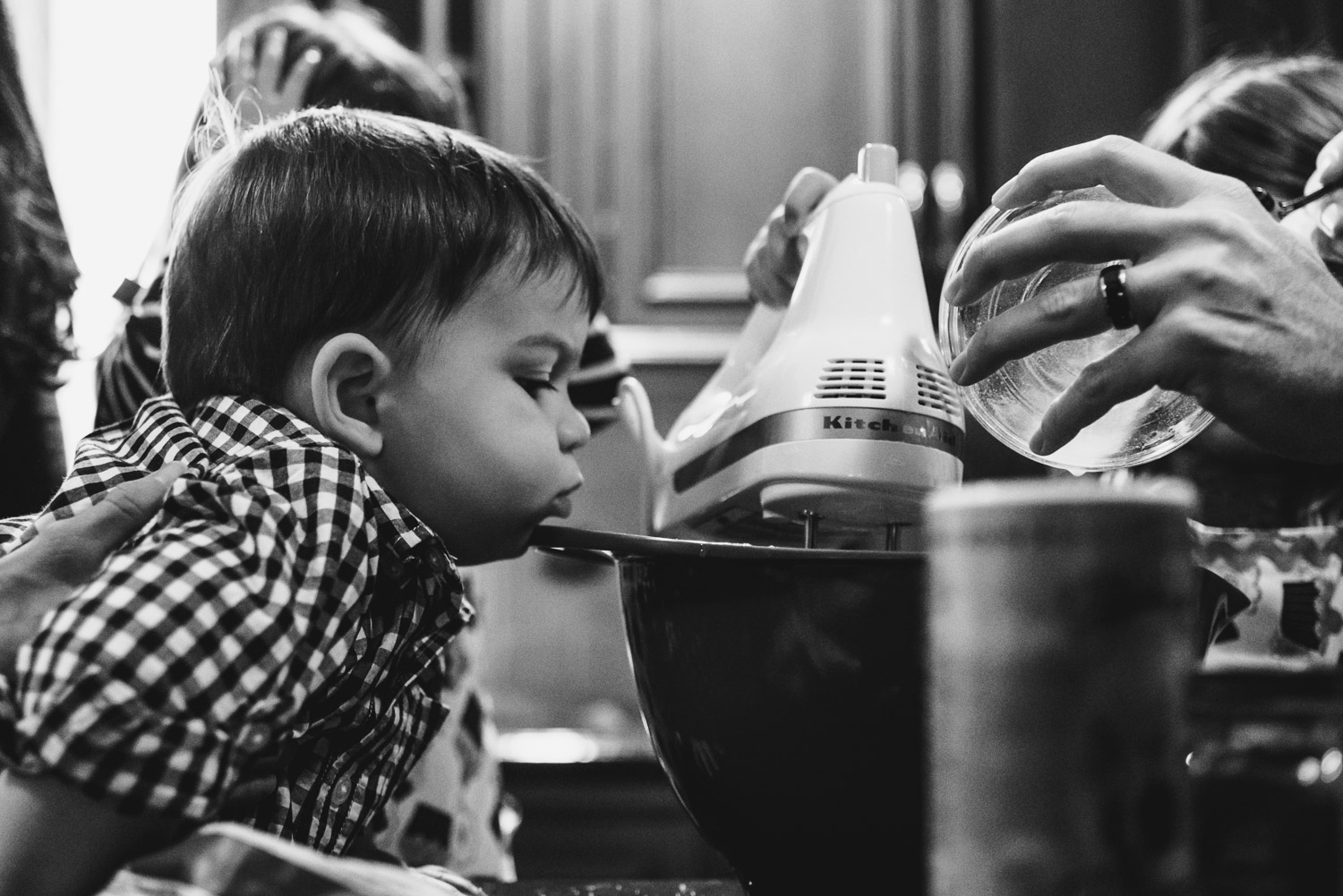 A baby boy peers over the edge of the mixing bowl while baking.