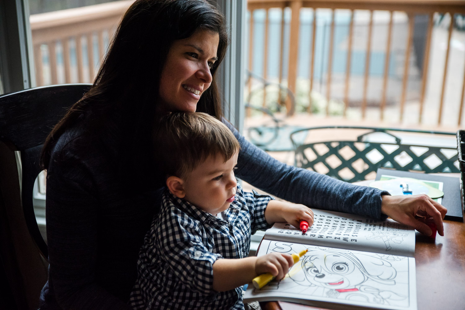 A mother sits with her toddler son while he colors.