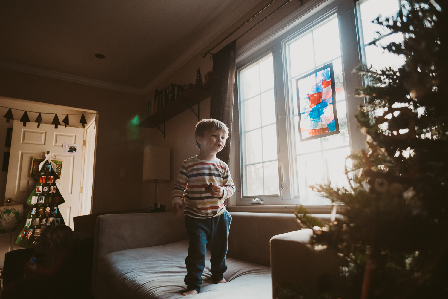 Little boy jumping on the couch next to the Christmas tree.