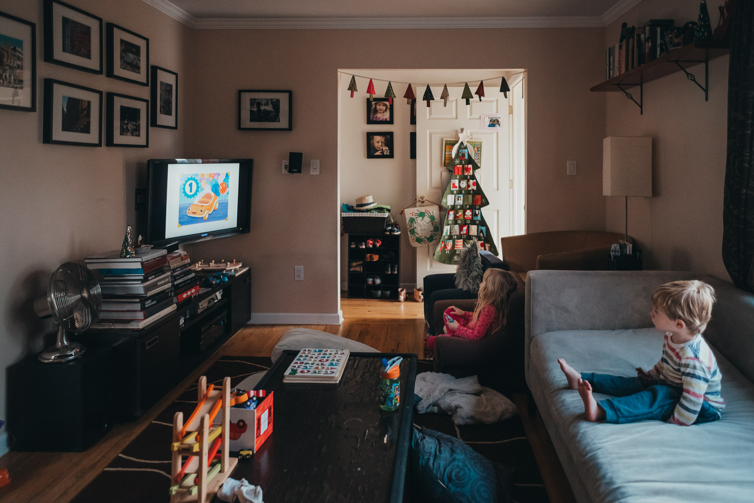 Kids watching TV in a living room decorated for Christmas.