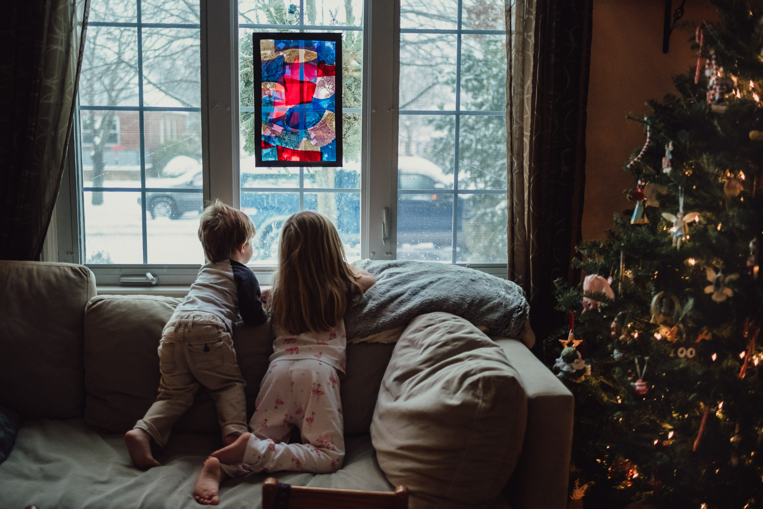 Kids watching the snow fall through a window next to the Christmas tree.