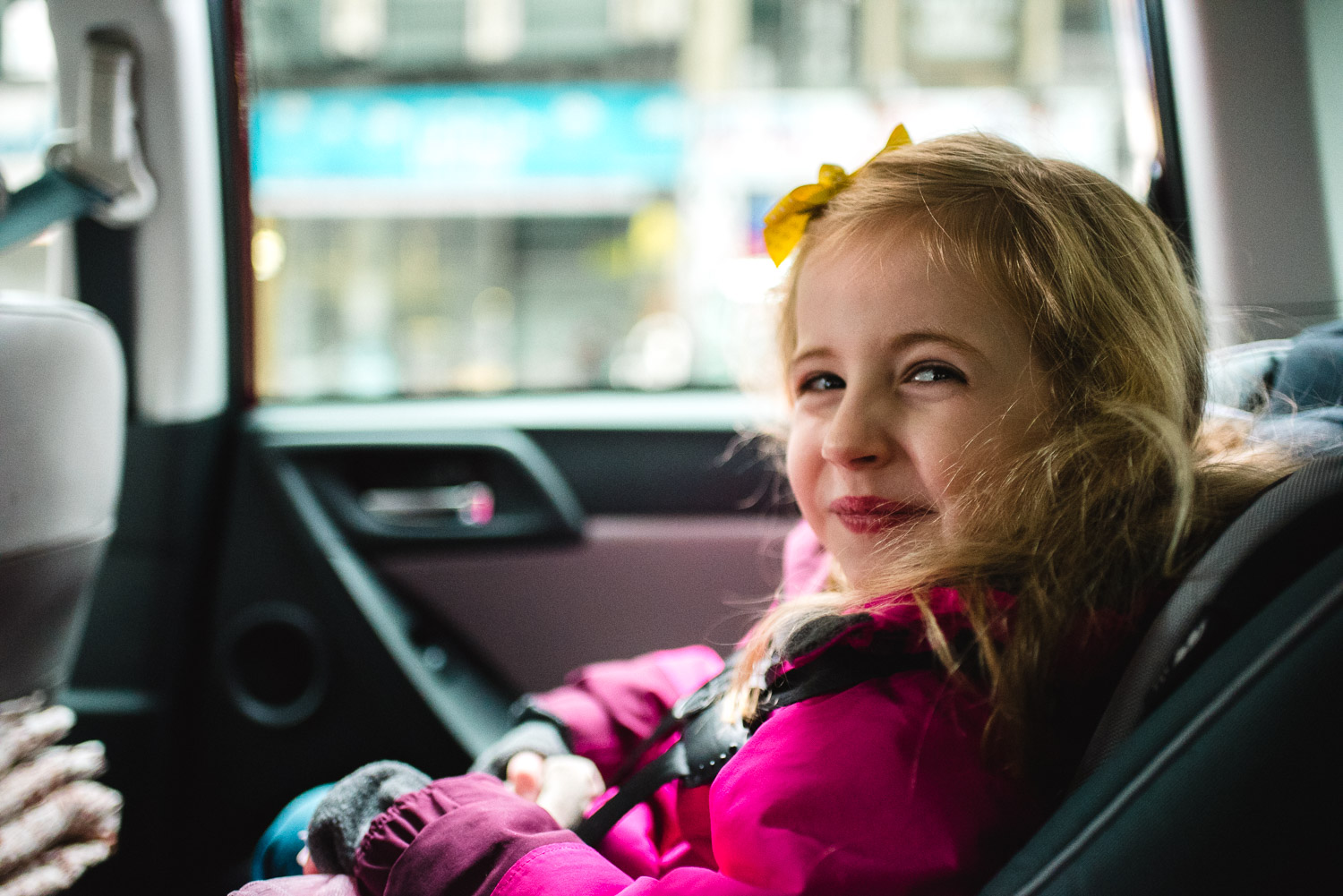 Little girl smiling in the car.