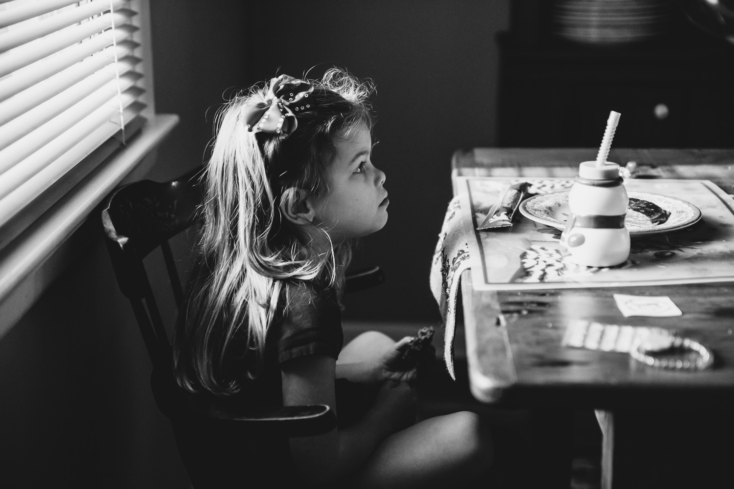 Little girl sitting at the dining room table.