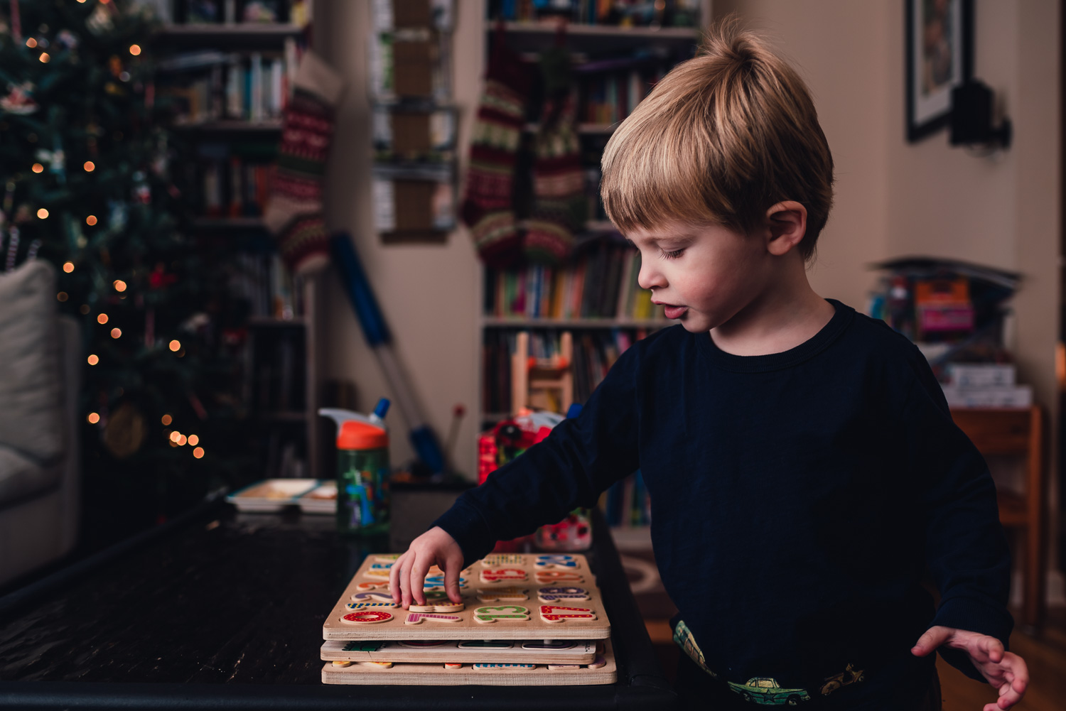 Little boy playing with a puzzle in the living room.