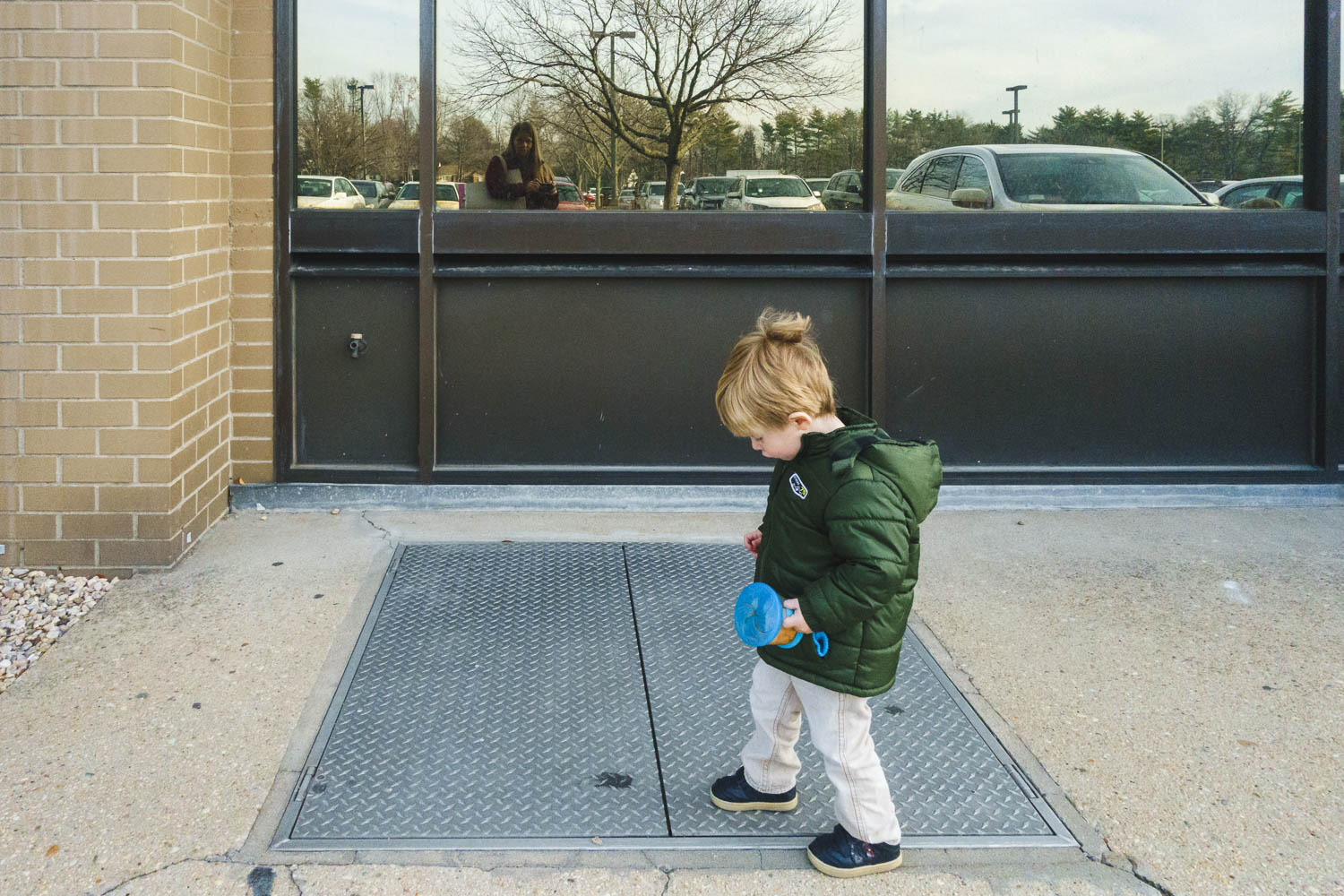 Little boy stomping on metal grate.