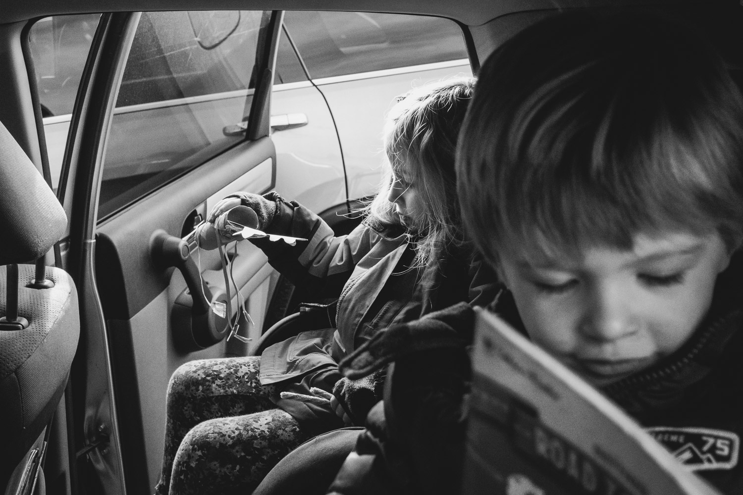 Kids reading books in the car.