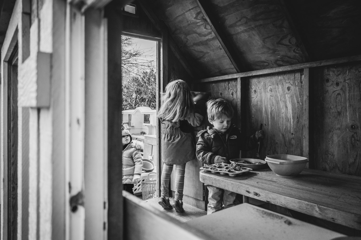 Kids playing in outdoor playhouse.