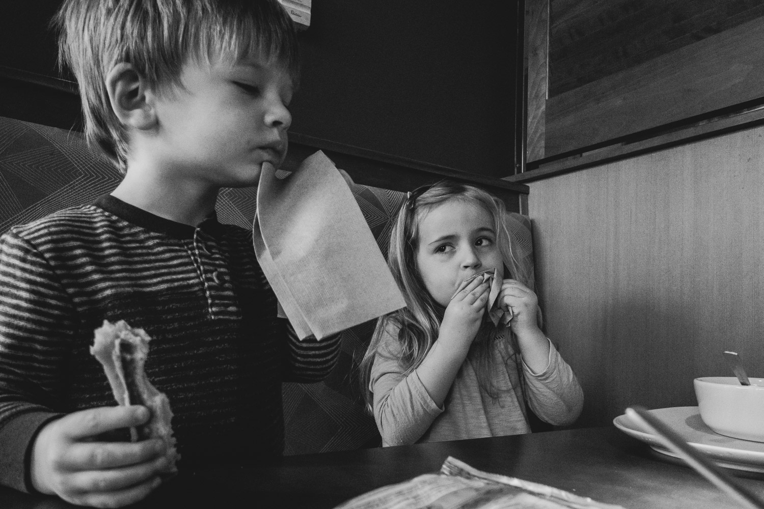 Children wiping their mouths with napkins at Panera Bread.